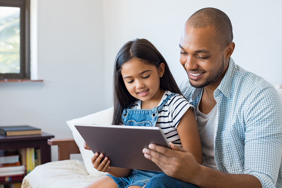 Client Center - Father and Daughter Smiling and Looking at a Tablet Together in Their Living Room