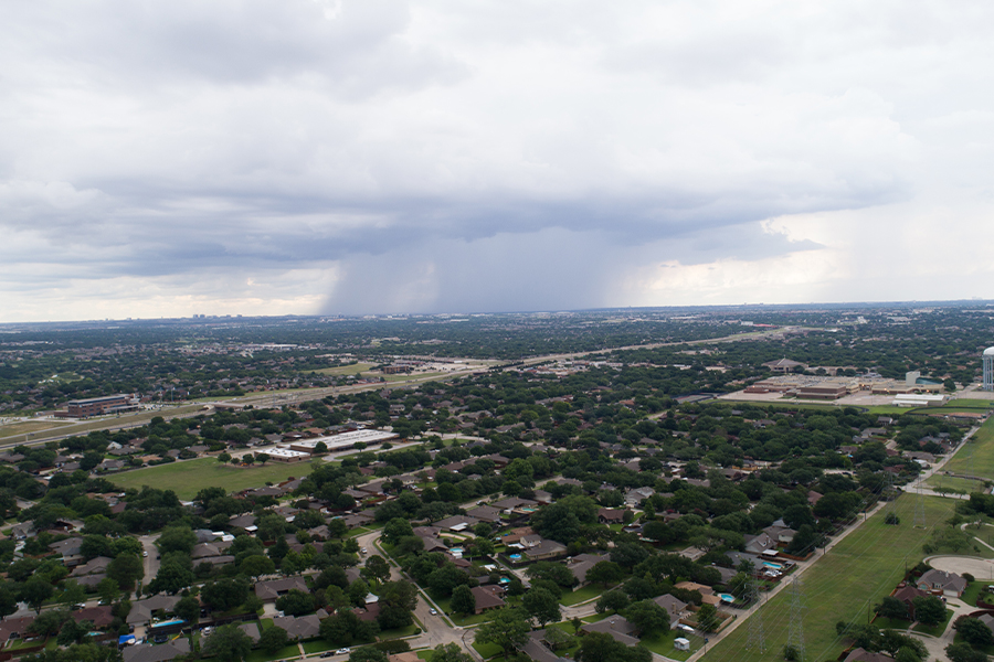 Contact - Aerial View of Suburban Texas Town on a Cloudy Day With a Rain Storm in the Distance