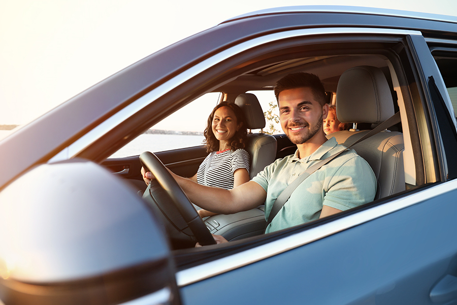 Personal Insurance - Happy Couple With Child Drivng in a Car on Sunny Day